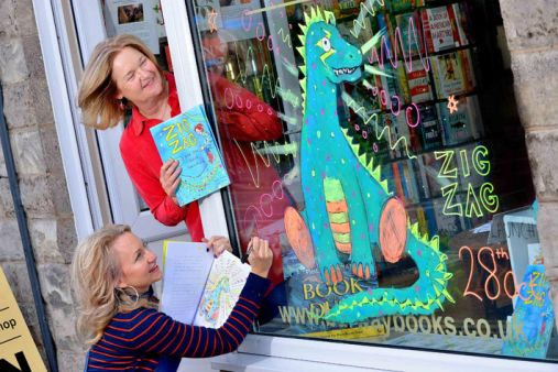 SOUTH COPYRIGHT SHROPSHIRE STAR STEVE LEATH 28/10/2017With video. Pic in Church Stretton at Burway Books, where it was the book launch for book 'Zig Zag'. Pictured is author: Barbara Townley from Church Stretton (in red) and illustrator: Cherie Jerrard from Shrewsbury (in stripes). With Zig Zag the dragon.